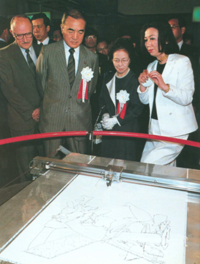 "In the US Pavilion at Tsukuba Expo 85, Japan Prime Minister Nakasone and company watch ""Aaron"" the robot draw."